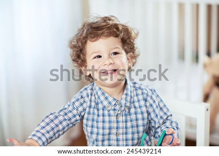 Portrait of happy smiling beautiful little boy in babyroom - checked shirt - stock photo