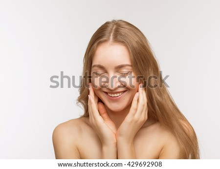 Portrait of happy smiling beautiful shirtless lady touching her face skin with both hands over white background in studio.