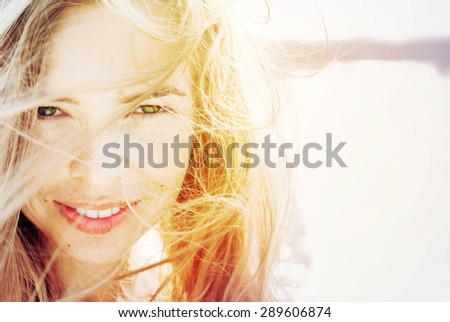Portrait Of Happy Smiling Beautiful Woman with Hair Blowing in the Wind. in Sunlight. Warm Color Toned - stock photo