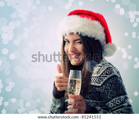 portrait of happy smiling beautiful young christmas woman winks with santa's hat and glass of champagne over blue snow background - stock photo