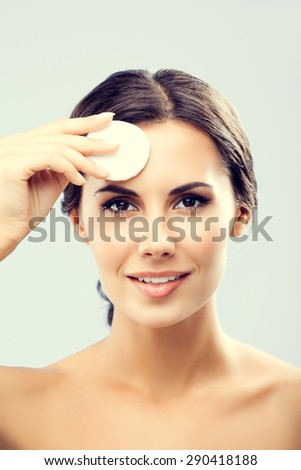 Portrait of happy smiling beautiful young woman cleaning skin by cotton pad - stock photo