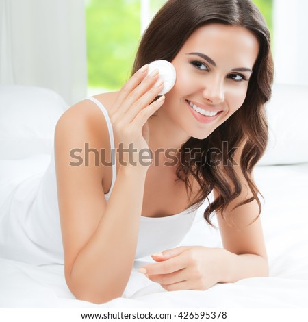 Portrait of happy smiling beautiful young woman cleaning skin by cotton pad, at home - stock photo