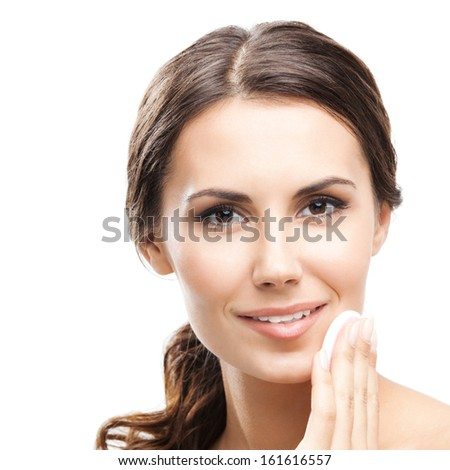 Portrait of happy smiling beautiful young woman cleaning skin by cotton pad, isolated over white background
