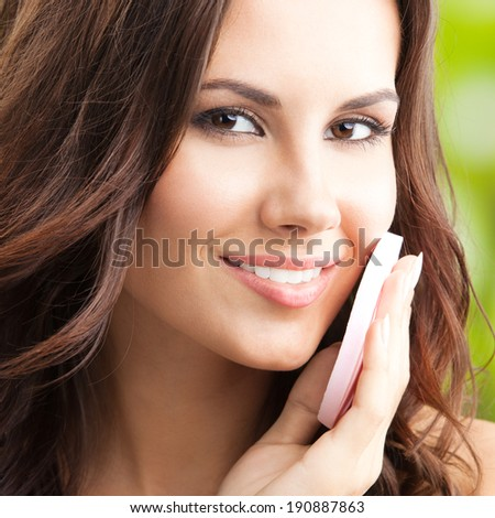 Portrait of happy smiling beautiful young woman cleaning skin by cotton pad, outdoor
