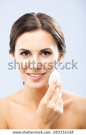 Portrait of happy smiling beautiful young woman cleaning skin by cotton pad, over grey background - stock photo