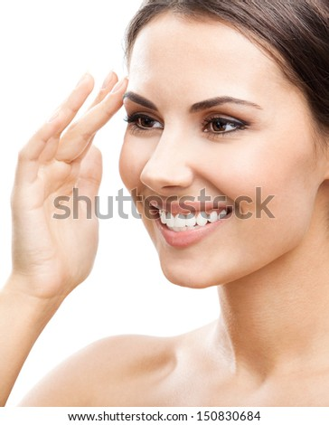 Portrait of happy smiling beautiful young woman looking at mirror and touching skin or applying cream, isolated over white background - stock photo