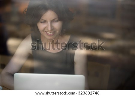 Portrait of happy smiling beautiful young woman sitting in front of window, using laptop, looking at the screen, female model working, interior shot through the glass - stock photo