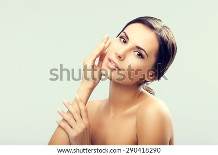 Portrait of happy smiling beautiful young woman touching skin or applying cream - stock photo