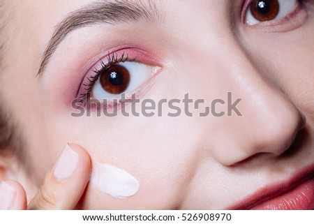 Portrait of  happy smiling beautiful young woman touching skin or applying cream