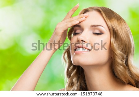 Portrait of happy smiling beautiful young woman touching skin or applying cream, outdoors - stock photo