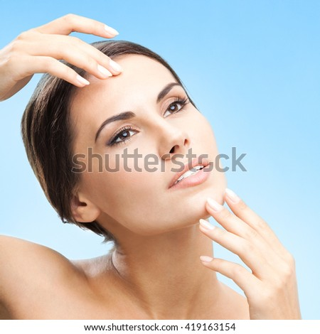 Portrait of happy smiling beautiful young woman touching skin or applying cream, over blue background - stock photo