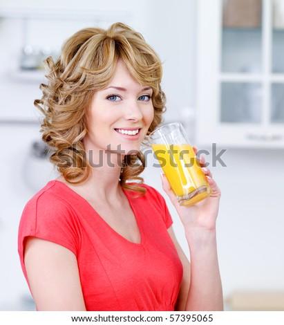 Portrait of happy smiling blonde woman drinking fresh orange juice in the kitchen - stock photo