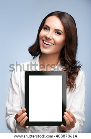 Portrait of happy smiling brunette businesswoman showing blank no-name tablet pc monitor, over grey background, with copyspace area for slogan or text message - stock photo