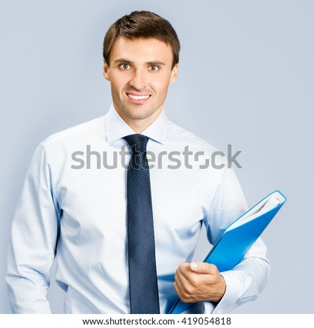 Portrait of happy smiling business man with blue folder, over grey background - stock photo