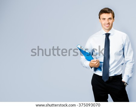 Portrait of happy smiling business man with blue folder, with copyspace, over grey background - stock photo