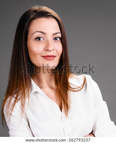 Portrait of happy smiling business woman on gray background