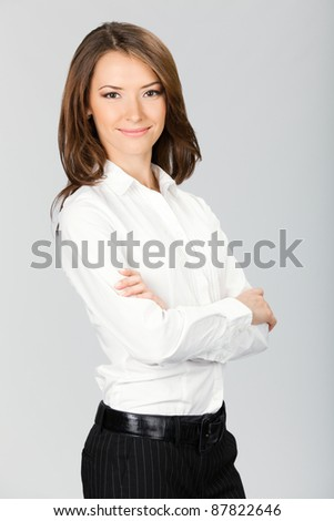 Portrait of happy smiling business woman, over grey background - stock photo