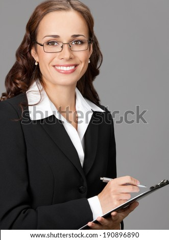Portrait of happy smiling business woman with clipboard, over gray background - stock photo