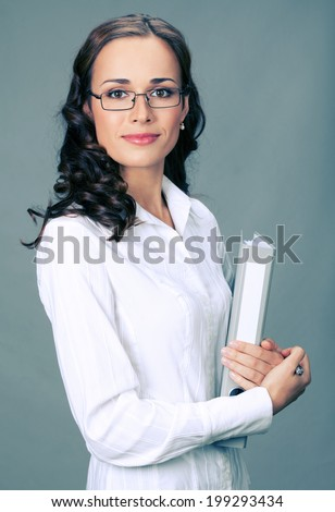 Portrait of happy smiling business woman with gray folder, over gray background - stock photo