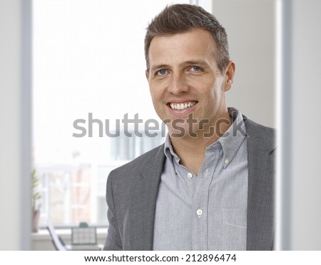 Portrait of happy smiling businessman at office. Suit with no tie, looking at camera. - stock photo