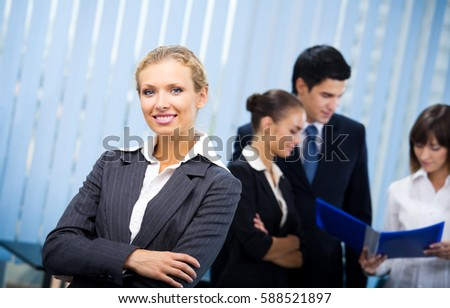 Portrait of happy smiling businesswoman and colleagues on background, at office. Teamwork, partnership, cooperation and business success concept.