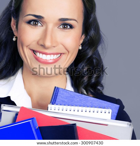 Portrait of happy smiling businesswoman with office supplies, posing at studio, over violet background - stock photo