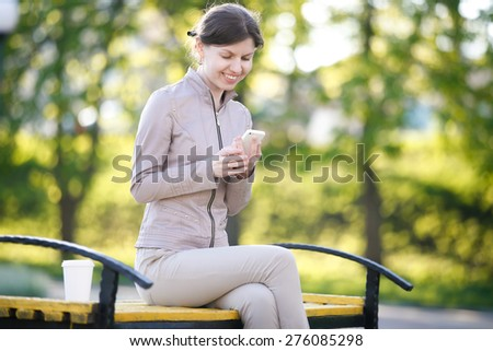 Portrait of happy smiling caucasian woman in park siting on the bench with takeaway drink, holding smartphone, using app, messaging, looking at screen - stock photo