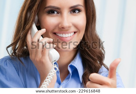 Portrait of happy smiling cheerful beautiful young business woman or support phone worker with thumb up geture