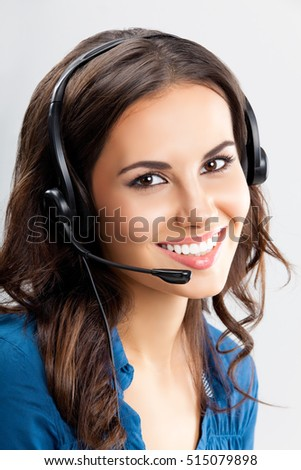 Portrait of happy smiling cheerful beautiful young female support phone operator in headset, over grey background. Caucasian brunette model in help servise and client consulting concept shot.