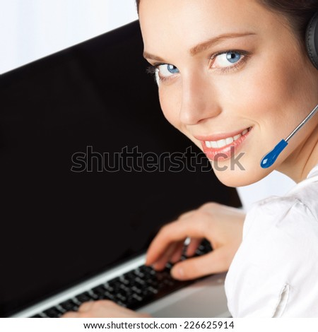 Portrait of happy smiling cheerful beautiful young support phone operator in headset with laptop, at office