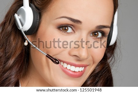 Portrait of happy smiling cheerful customer support phone operator in headset, over gray background - stock photo
