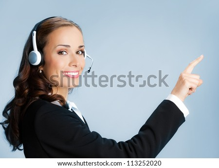 Portrait of happy smiling cheerful customer support phone operator in headset pointing at something, over blue background