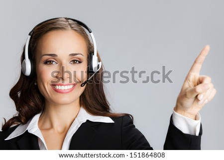 Portrait of happy smiling cheerful customer support phone operator in headset pointing at something, over grey background - stock photo