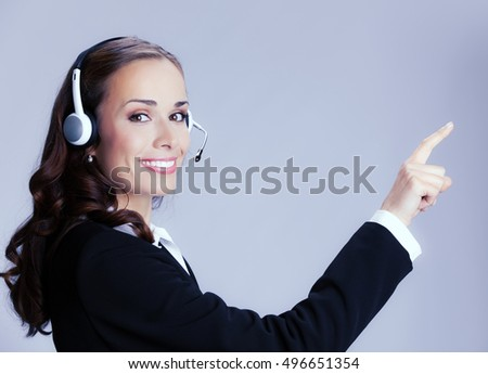 Portrait of happy smiling cheerful customer support phone operator in headset pointing at something, over grey background. Brunette woman in help servise and client consulting concept shoot.