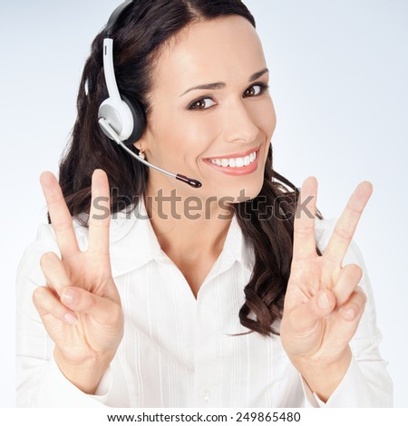 Portrait of happy smiling cheerful customer support phone operator in headset showing two fingers, against grey background - stock photo