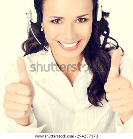 Portrait of happy smiling cheerful customer support phone operator or businesswoman in headset showing thumbs up hand sign gesture