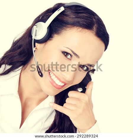Portrait of happy smiling cheerful customer support phone operator or businesswoman in headset with call me gesture - stock photo