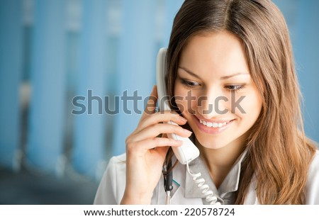 Portrait of happy smiling cheerful young female doctor on phone, at office - stock photo