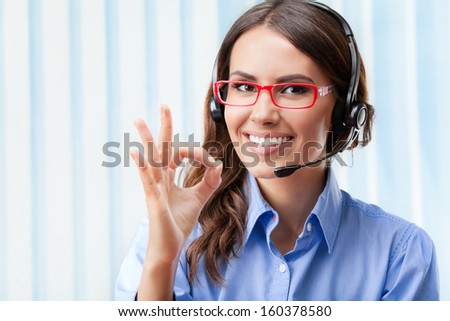 Portrait of happy smiling cheerful young support phone operator in headset, showing okay gesture, at office - stock photo