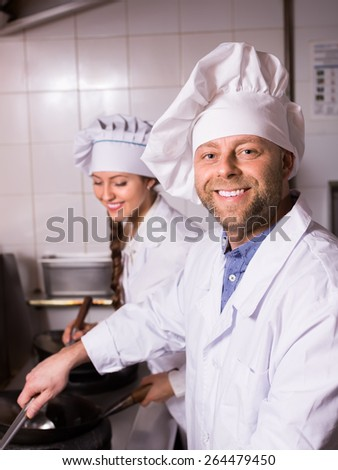 Portrait of happy smiling chef with beautiful young female assistant at kitchen in cafe