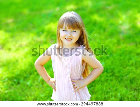 Portrait of happy smiling child little girl on the grass in summer day - stock photo