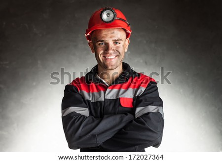 Portrait of happy smiling coal miner with his arms crossed against a dark background