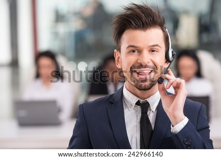 Portrait of happy smiling customer support phone operator at workplace. - stock photo