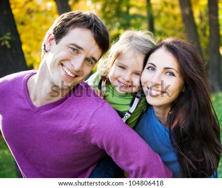 Portrait of happy smiling family in autumn park - stock photo