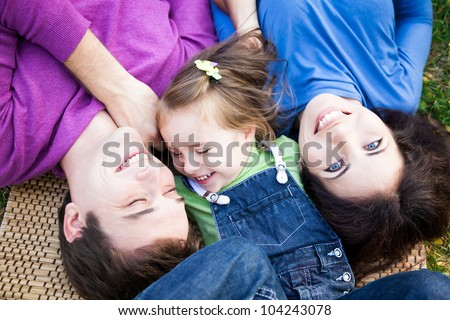 Portrait of happy smiling family lying outdoors in autumn park - stock photo