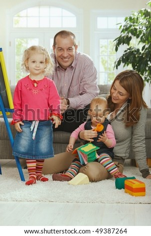 Portrait of happy smiling family of dad, mum and two baby girls at home. - stock photo