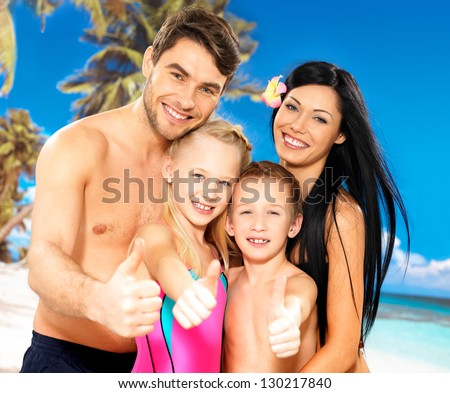 Portrait of  happy smiling family with thumbs up sign  at tropical beach - stock photo