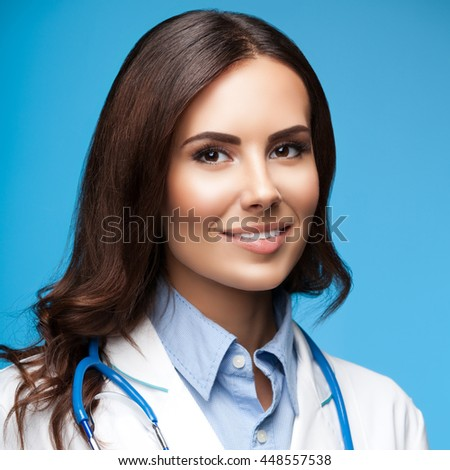 Portrait of happy smiling female doctor, on blue background - stock photo