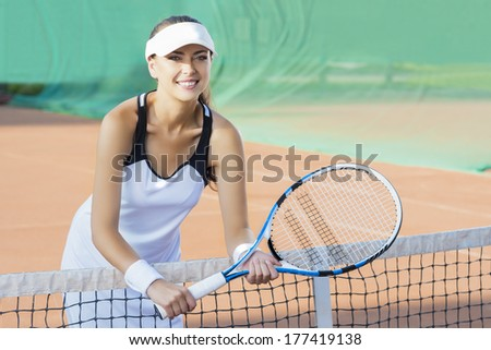 Portrait of Happy Smiling Female Tennis Player at Court Standing Close To the Net. Horizontal Image - stock photo