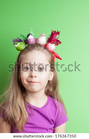 Portrait of happy smiling five years old blond caucasian child girl with colorful birds on head - pastel green background. Careless childhood and spring concept - layout with free text space. - stock photo